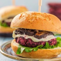 Beet Greens Lentil Burgers-closeup view-small-square-assembled with green leaf lettuce, mayonnaise, soy sauce braised shiitake mushrooms between gluten-free buns