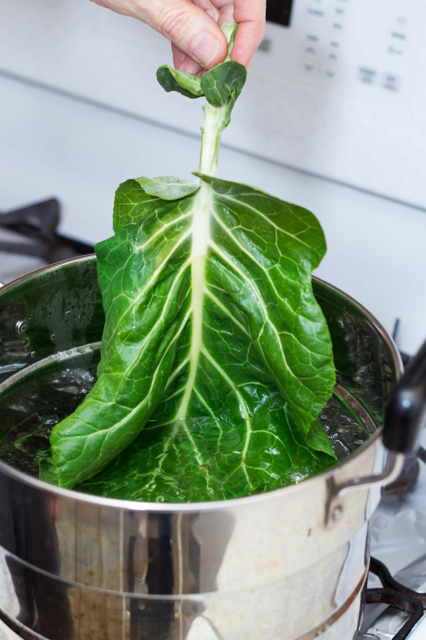 Grain-free Collard Green Rolls-Dipping collard green leaf in a pot of boiling water