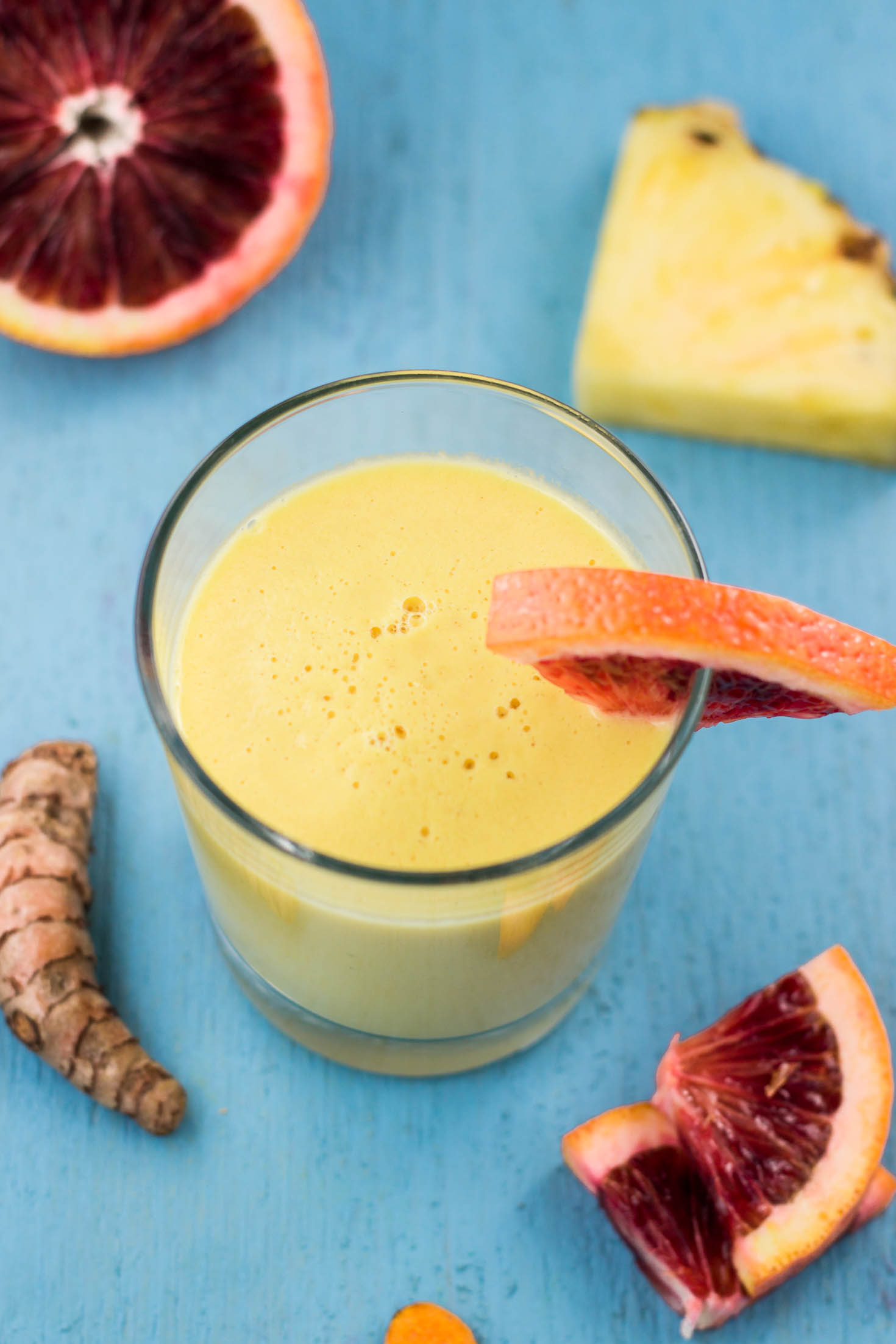 Cardamom Turmeric Spiced Golden Tropical Smoothie-topview in a glass with blood orange garnish