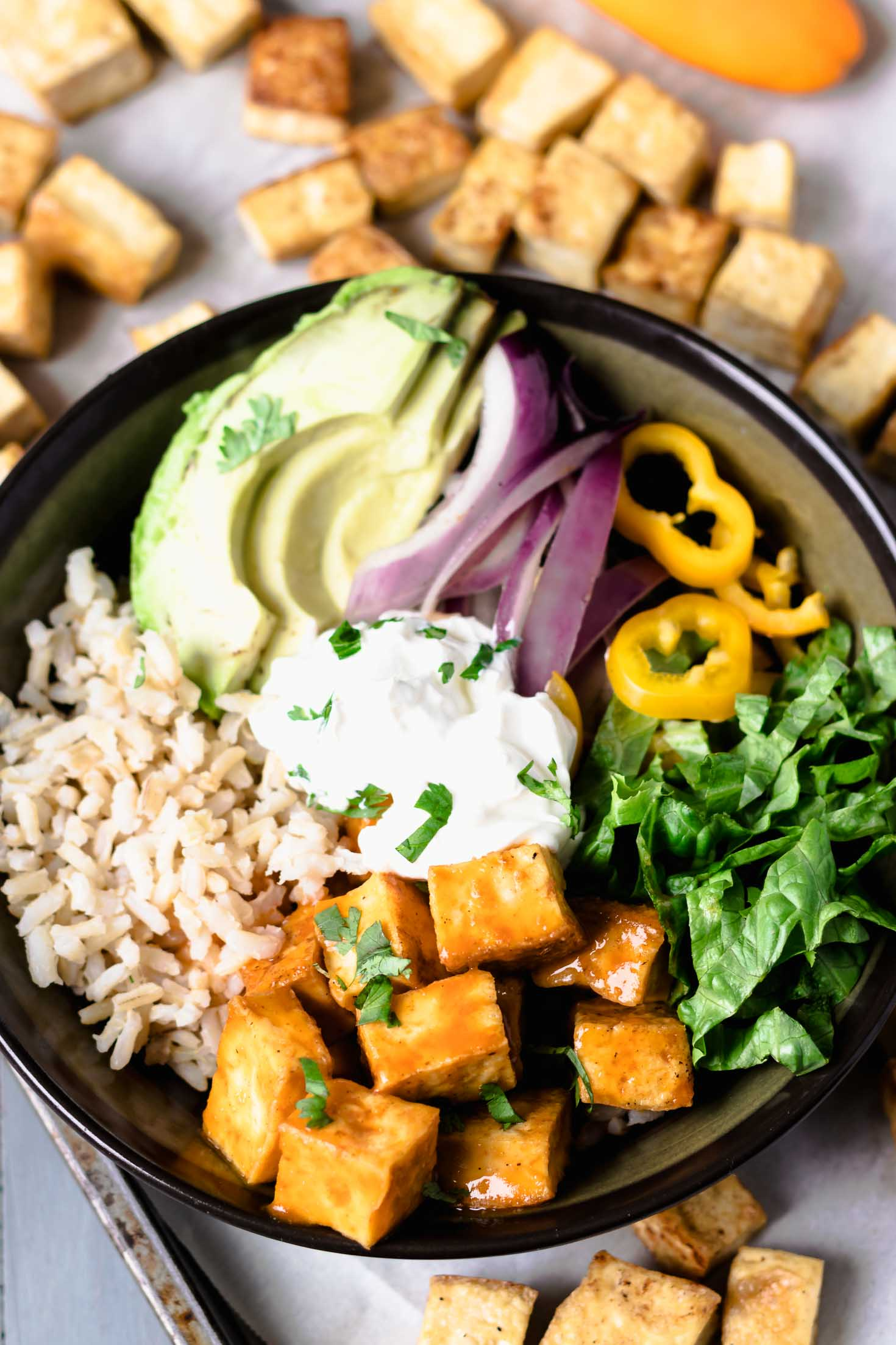 vegan buffalo tofu burrito bowl -top view with roasted tofu on baking sheet