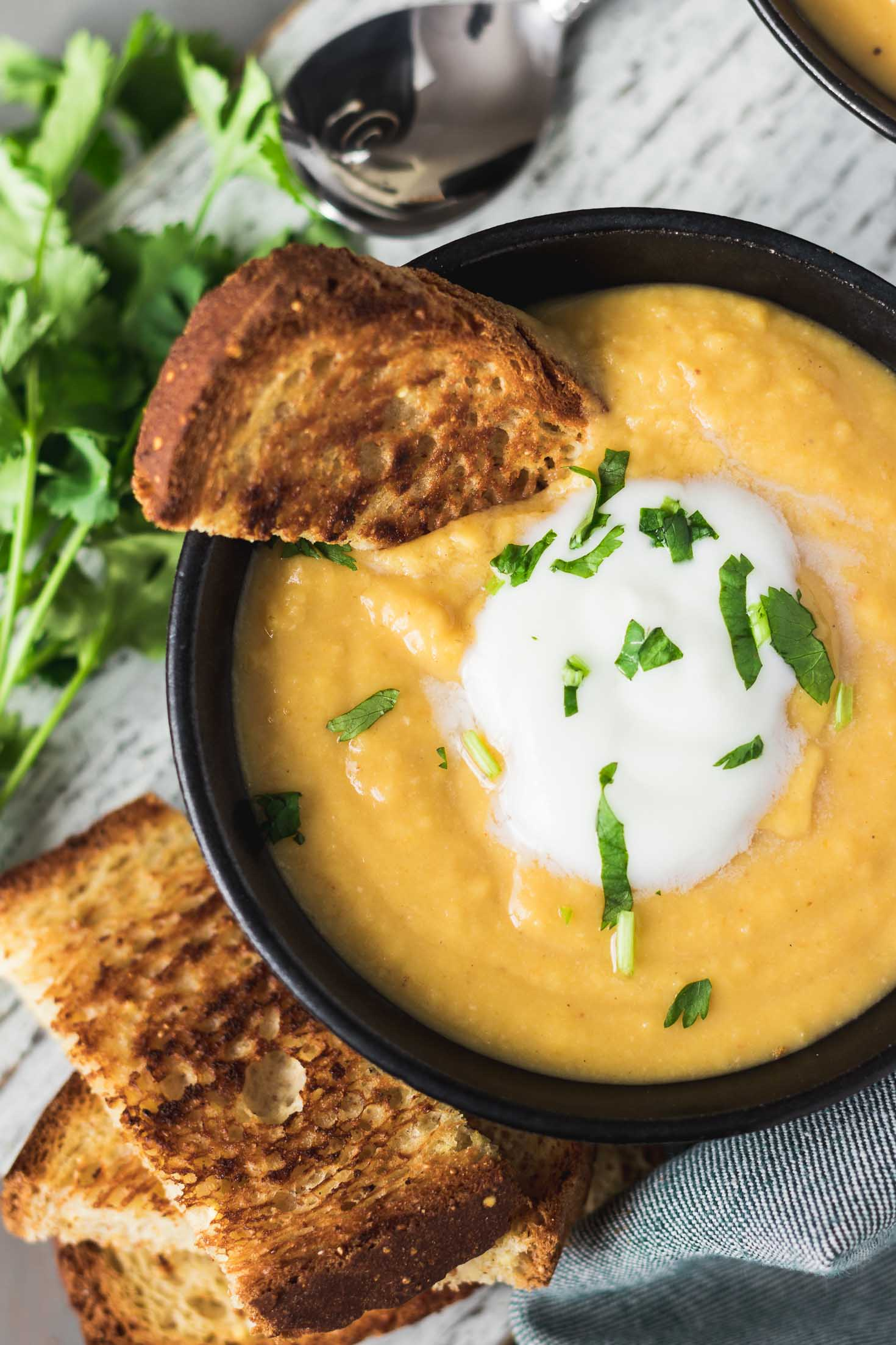 Navy Bean Garam Masala Carrot Soup-topview-soup in one bowl with toasted bread and garnished with yogurt and fresh cilantro leaves