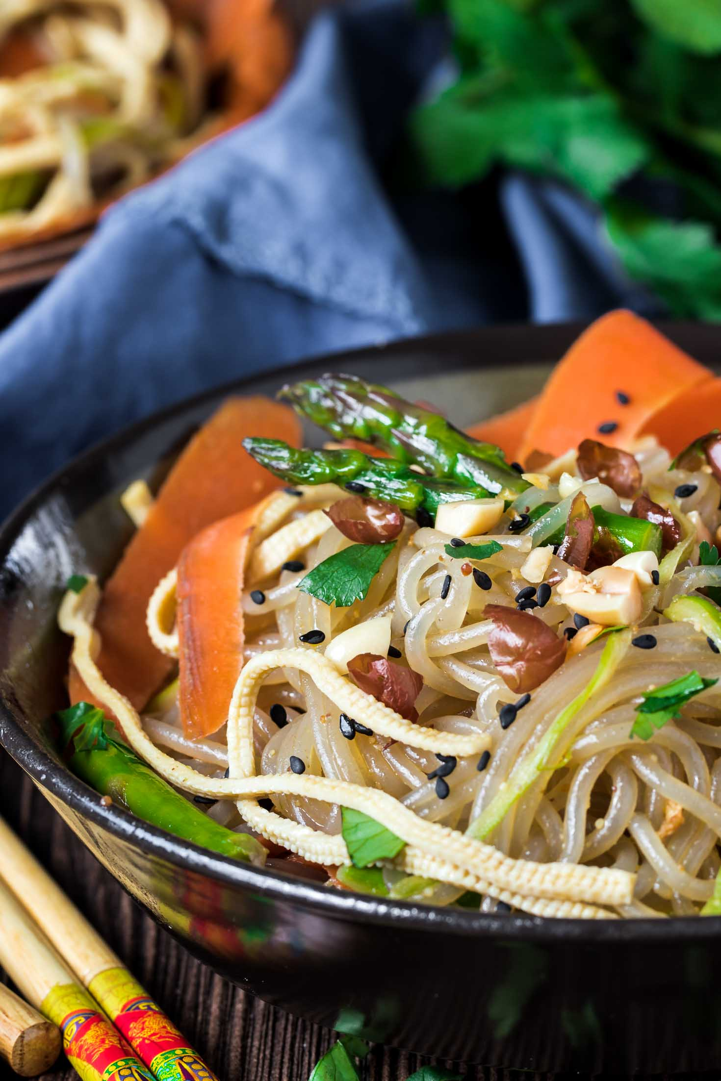Vegan Korean Glass Noodle Stir-Fry with Tofu Slices (JapChae)-close up view-a bowl of noodles garnished with roasted peanuts and fresh cilantro on a board