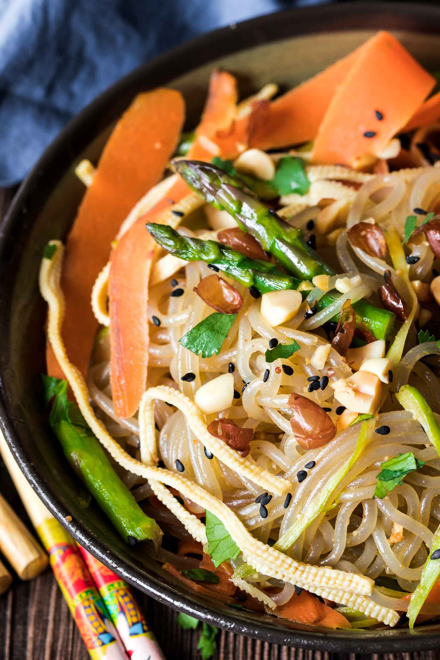 Vegan Korean Glass Noodle Stir-Fry with Tofu Slices (JapChae)-top view-a bowl of noodles garnished with roasted peanuts and fresh cilantro on a board