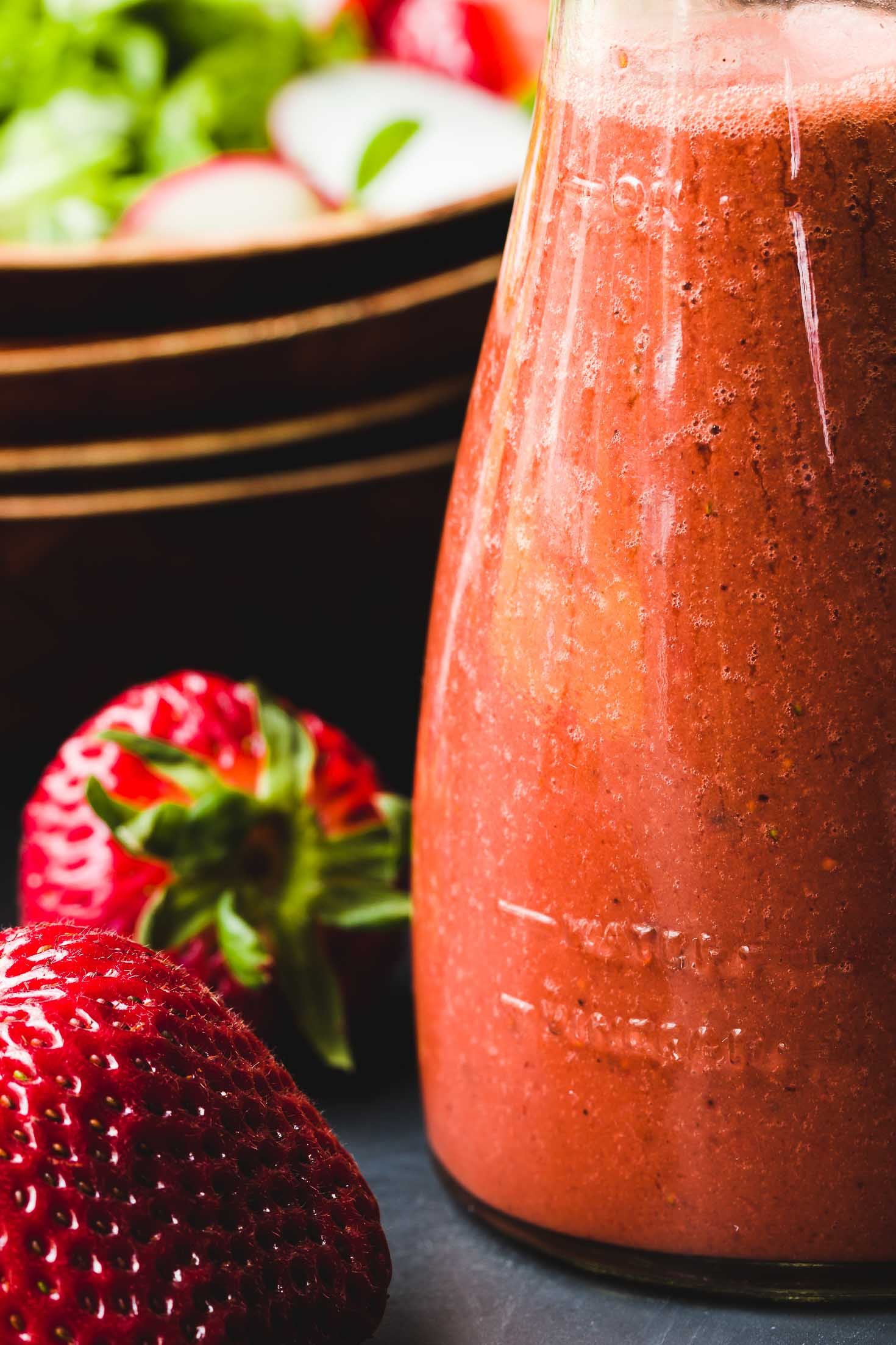 Mustard Seeds Strawberry Balsamic Vinaigrette Dressing-closeup view-dressing in a glass jar and two strawberries on the left side