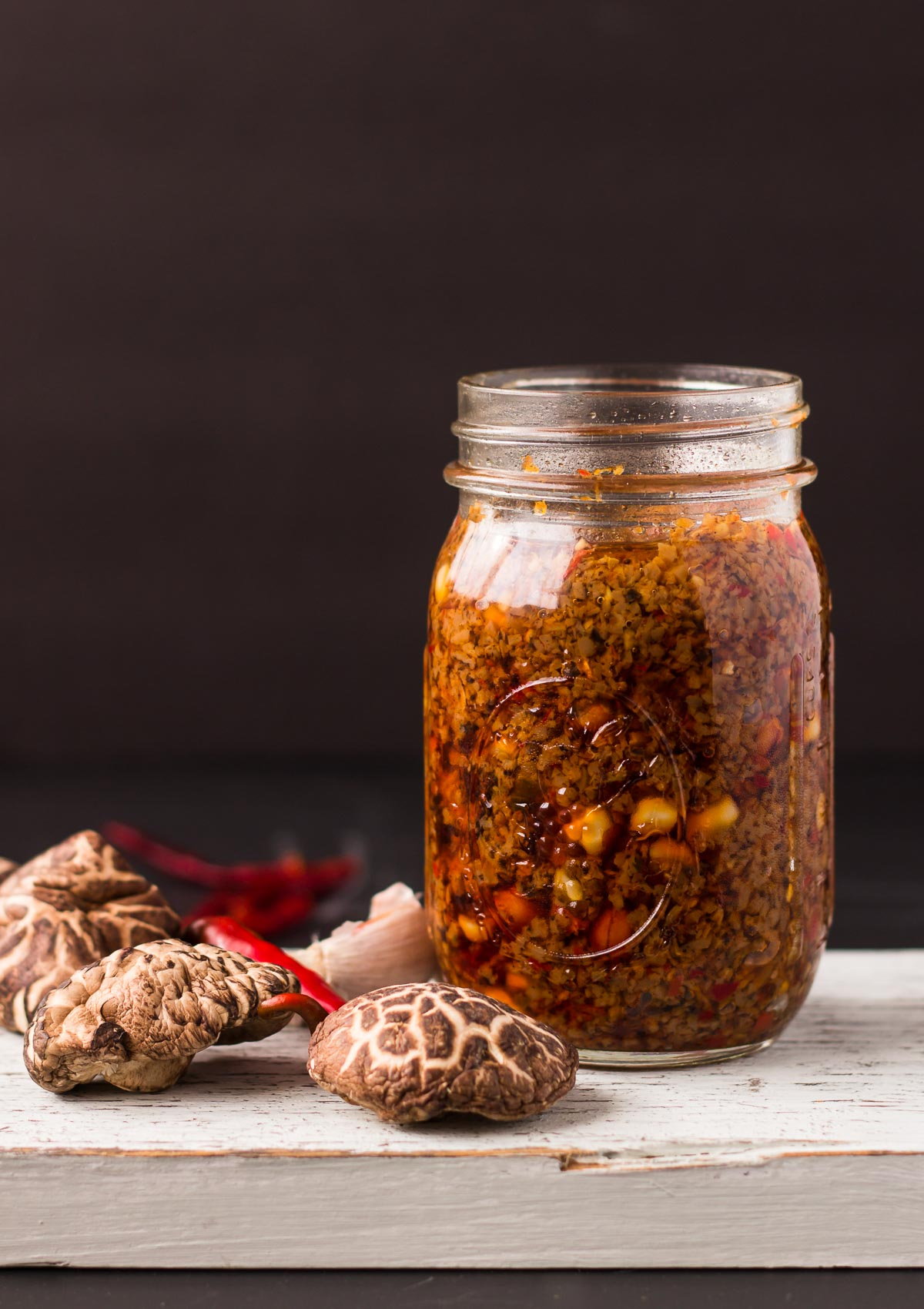 Shiitake Mushroom Chili Sauce-front view-in a glass jar-red chilis and dried shiitake mushrooms on the left side