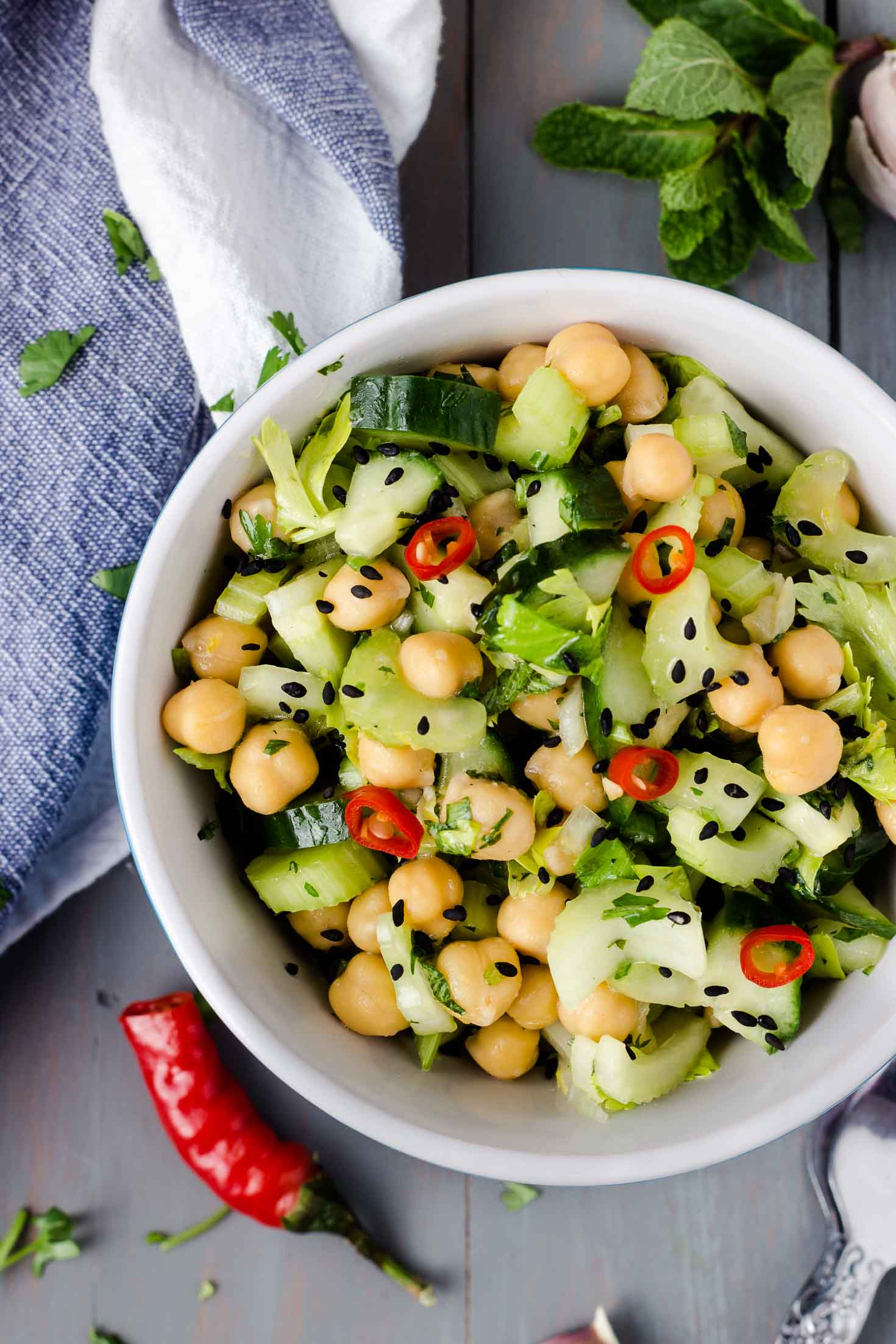 Celery Cucumber Chickpea Salad-top view in a bowl-garnished with black sesame seeds and chopped red chili pepper