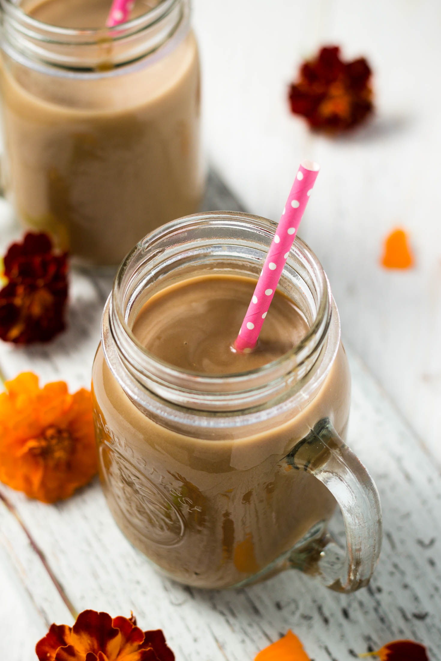 top view of pumpkin spice latte smoothie with a pink straw in a glass jar, two jars