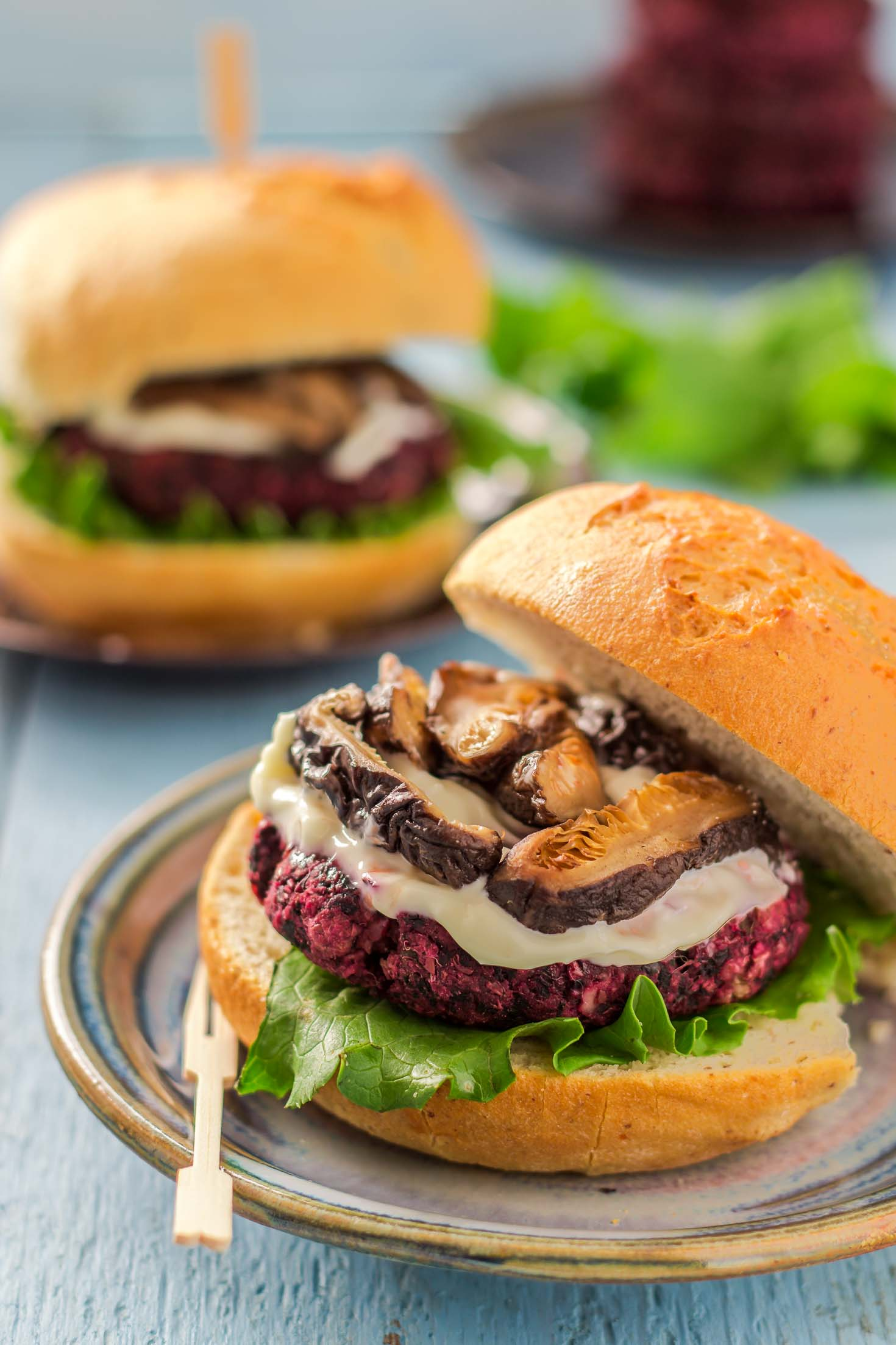 Beet Greens Lentil Burgers-top view-assembled with green leaf lettuce, mayonnaise, soy sauce braised shiitake mushrooms between gluten-free buns