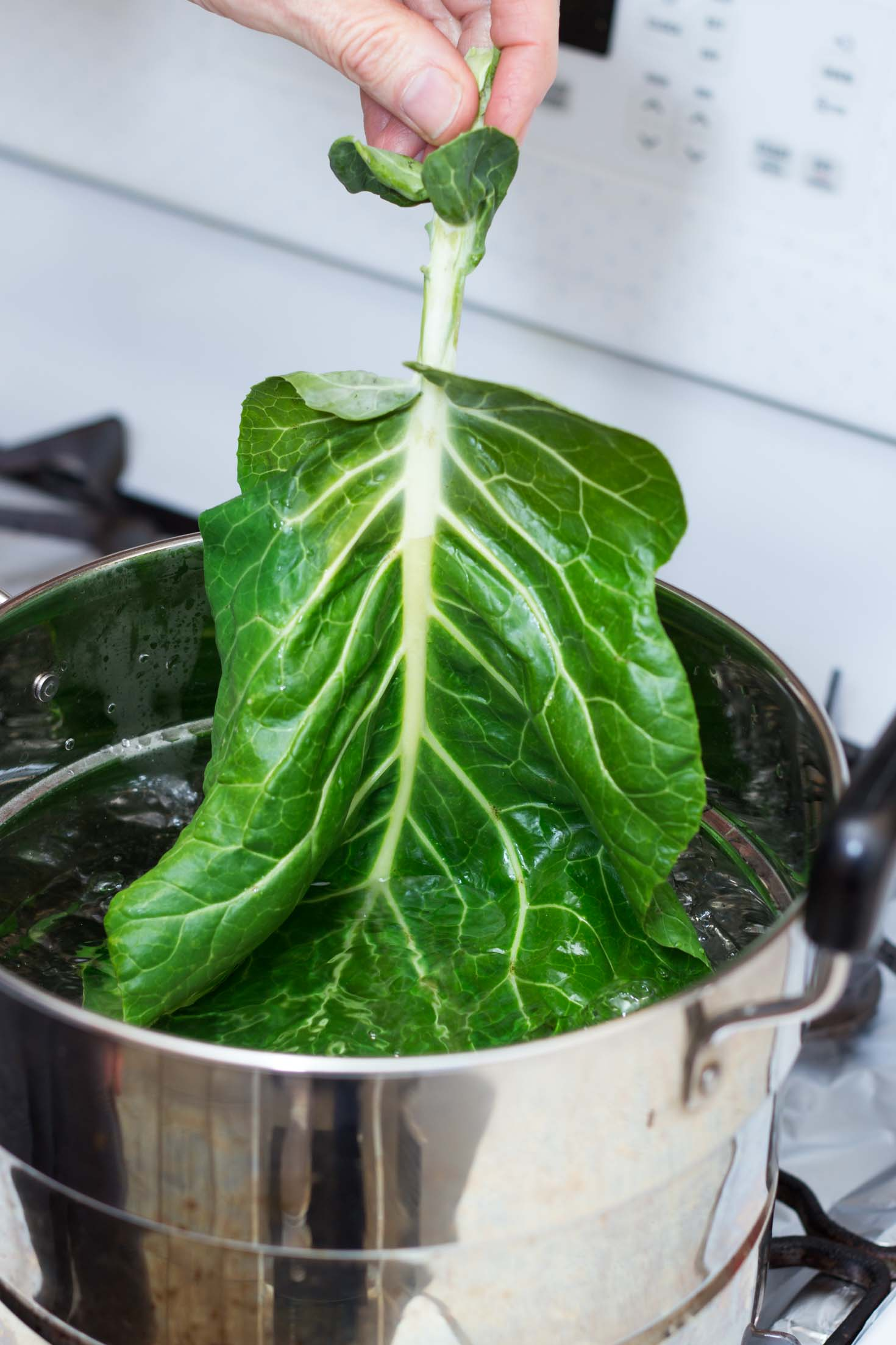Grain-free Collard Green Rolls-Dipping collard green leaf in a pot of boiling water