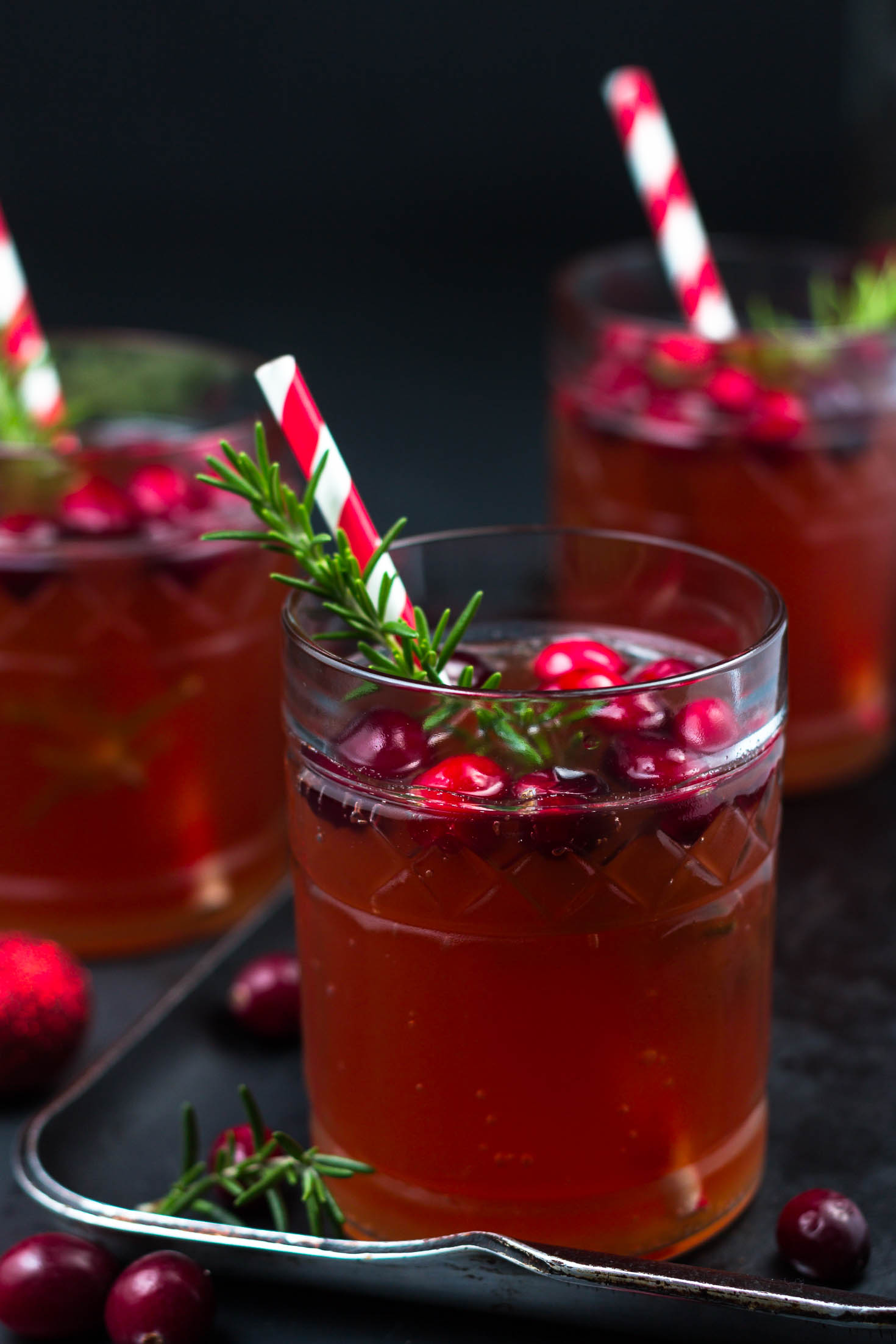 Sparkling Cranberry Rosemary Kefir Punch-closeup view with 3 glasses of kefir punch garnished with fresh rosemaries and cranberries.