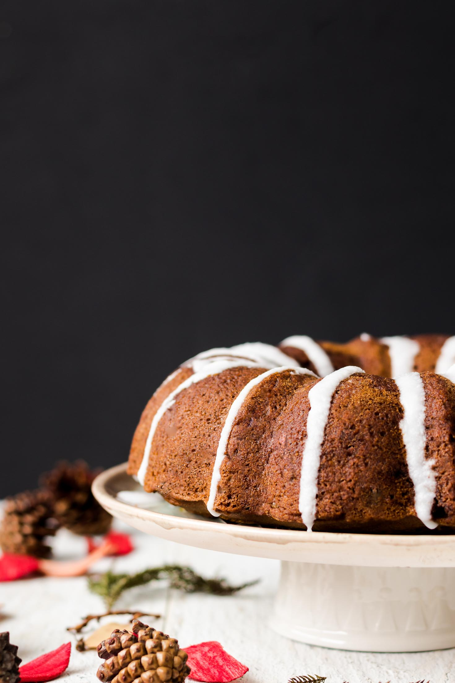 Banana Gingerbread Bundt Coffee Cake-side view-whole coffee cake is glazed with coconut glaze and is placed on a cake plate