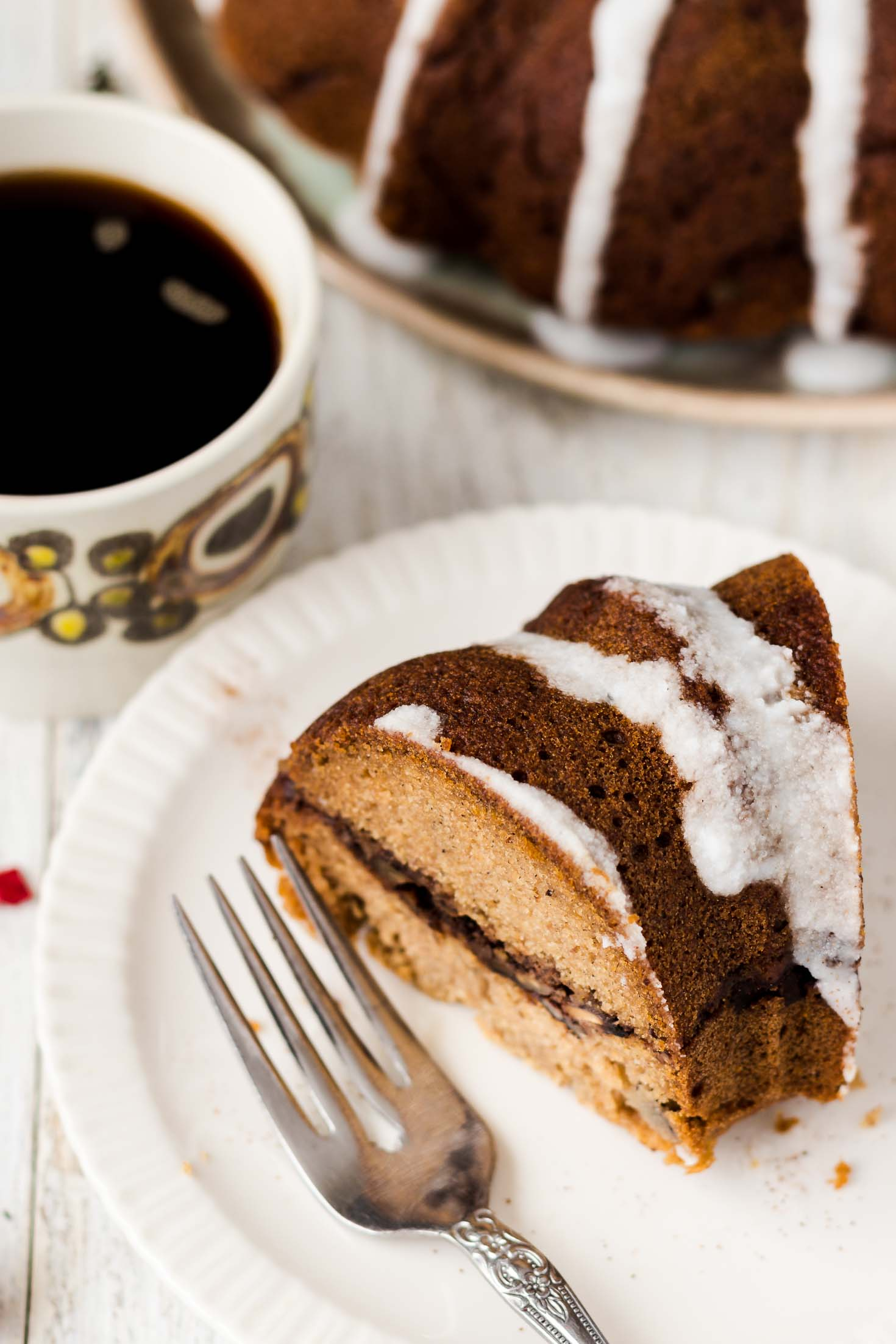 Banana Gingerbread Bundt Coffee Cake-top view-one slice of coffee cake next to a cup of black coffee
