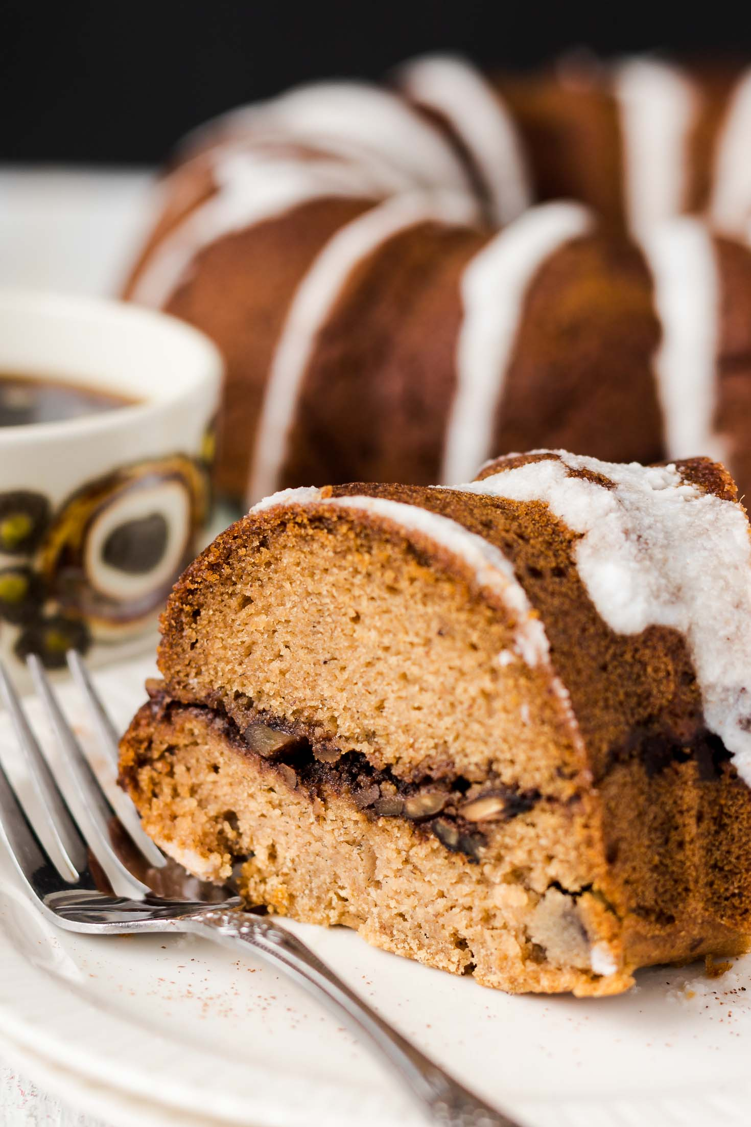 Banana Gingerbread Bundt Coffee Cake-side view-one slice of coffee cake next to a cup of black coffee