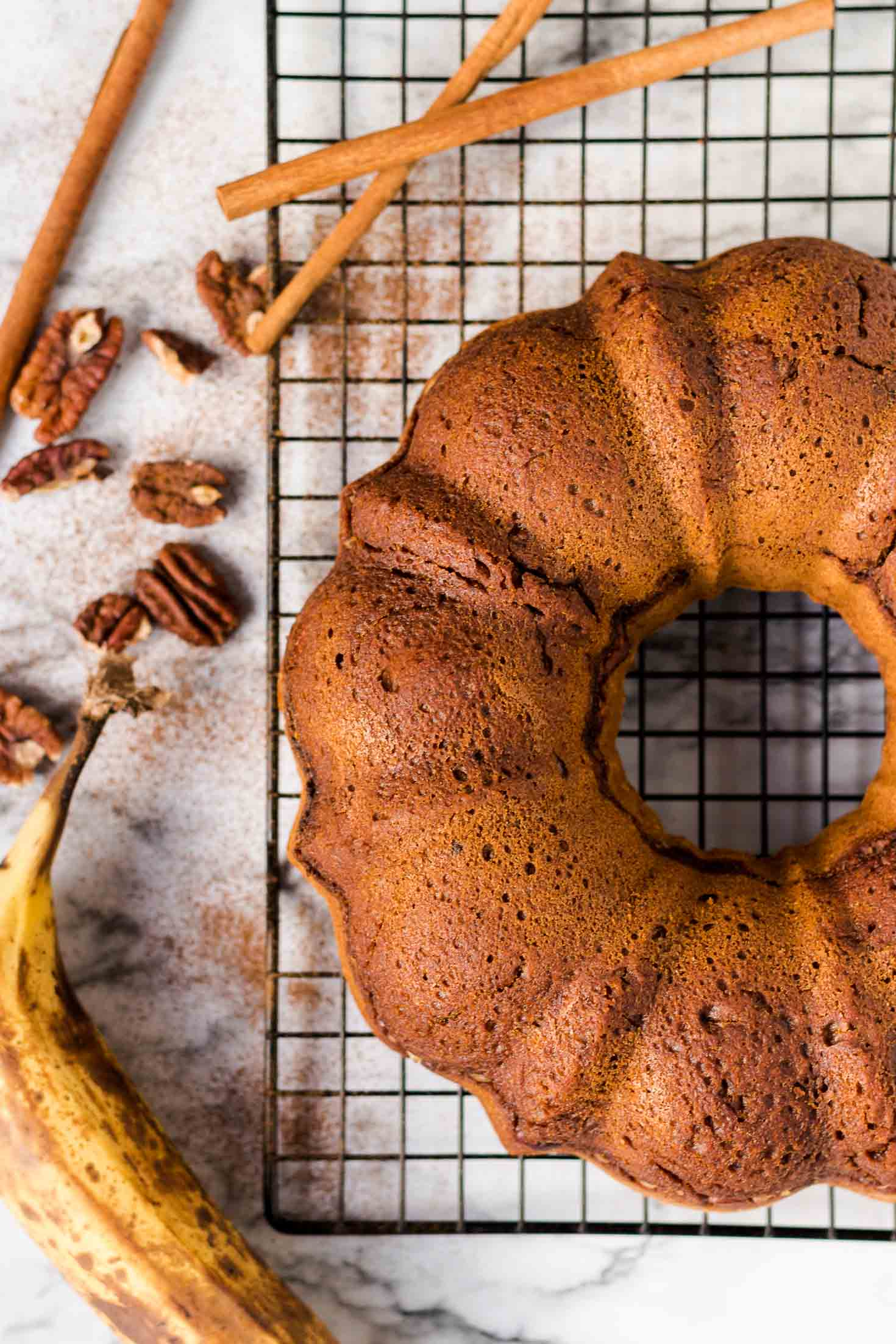 Banana Gingerbread Bundt Coffee Cake-top view-cake on a cooling rack-banana-pecan and cinnamon on the sides as prop