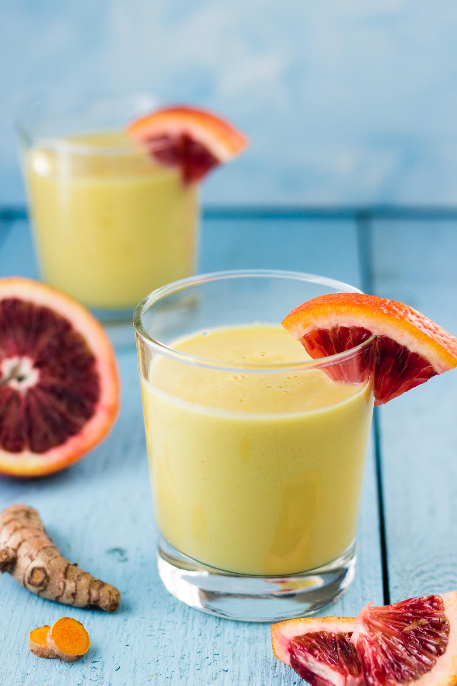 Cardamom Turmeric Spiced Golden Tropical Smoothie-sideview in a glass with blood orange garnish
