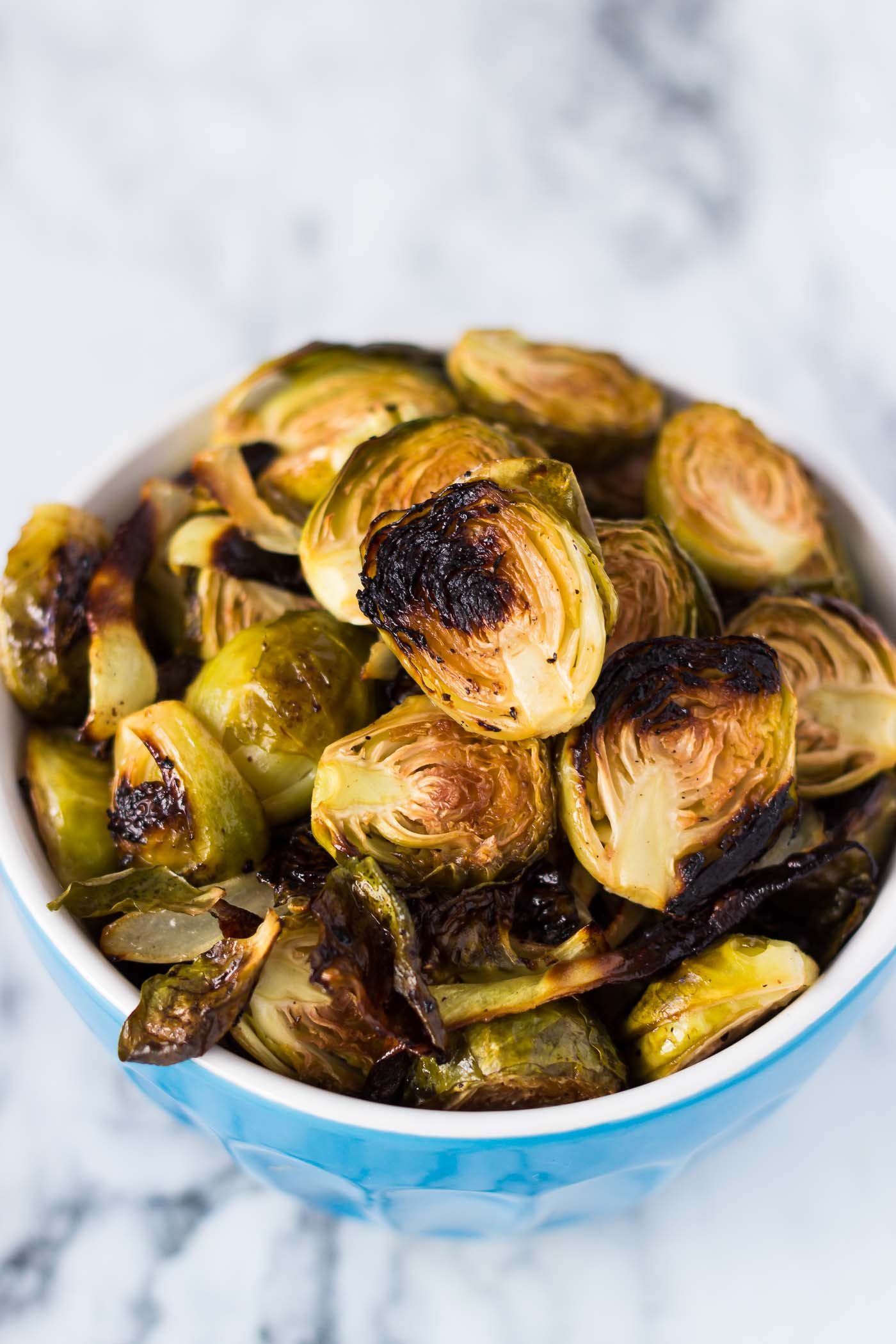 Sheet Pan Rosemary Garlic Brussels Sprouts-45 degree top view angle-roasted sprouts in a blue bowl without garnishing