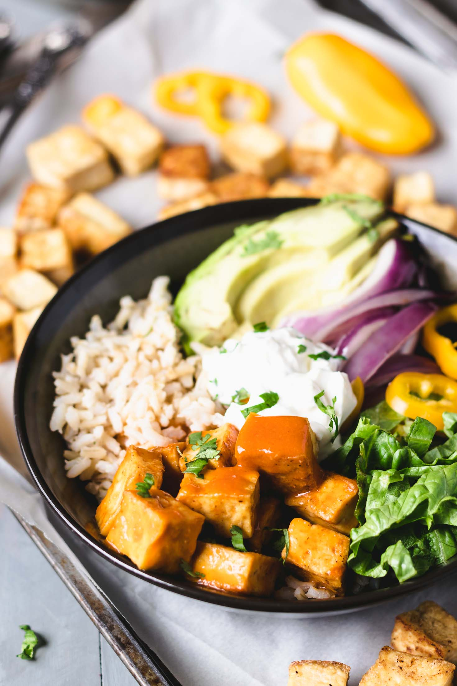 vegan buffalo tofu burrito bowl-top-side view-buffalo tofu-brown rice-leaf lettuce-sauteed red onion-yellow pepper-vegan sour cream garnished with chopped cilantro in a round bowl