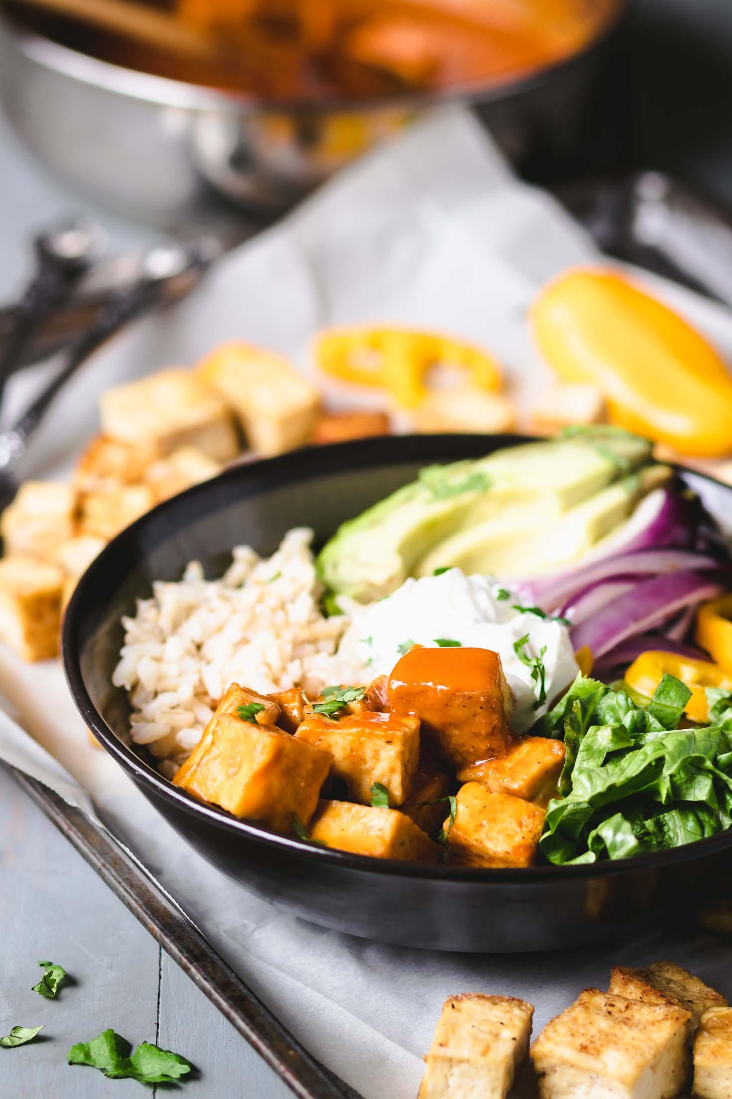 Vegan buffalo tofu burrito bowl-side view-buffalo tofu-brown rice-leaf lettuce-sauteed red onion-yellow pepper-vegan sour cream garnished with chopped cilantro in a round bowl