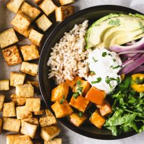 Vegan Buffalo tofu burrito bowl-top view-square image-buffalo tofu-brown rice-leaf lettuce-sauteed red onion-yellow pepper-vegan sour cream garnished with chopped cilantro in a round bowl