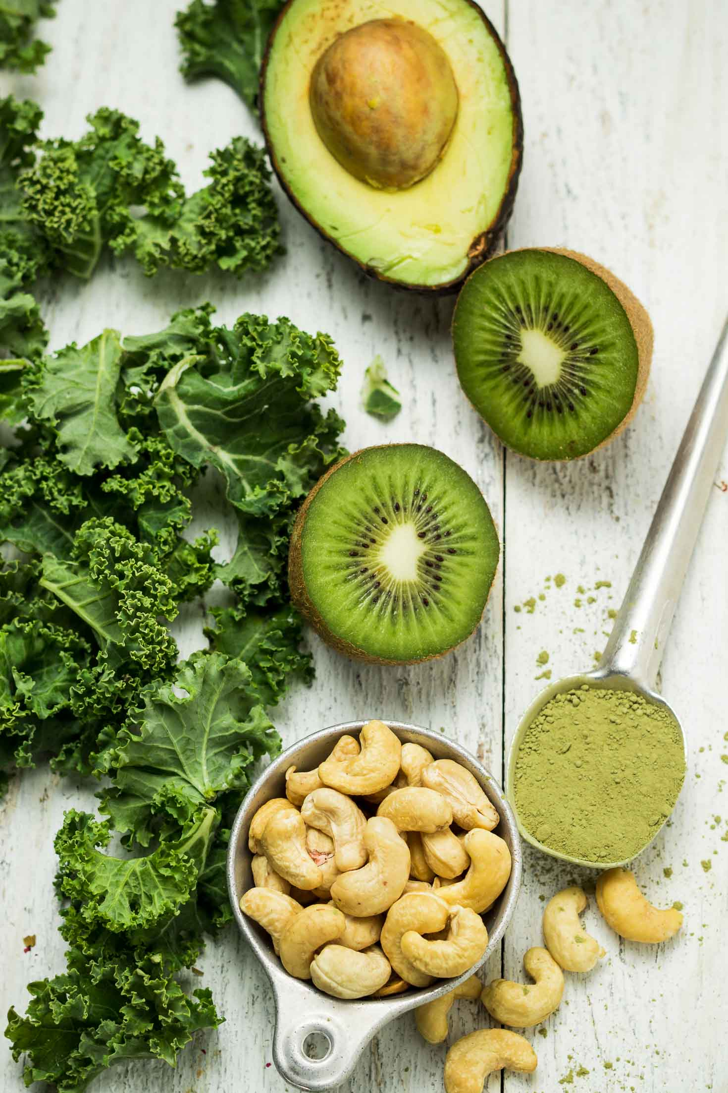 Green Kiwi Matcha Protein Smoothie-top view-ingredients-cashew nuts, matcha powder, kale leaves, kiwifruit, avocado