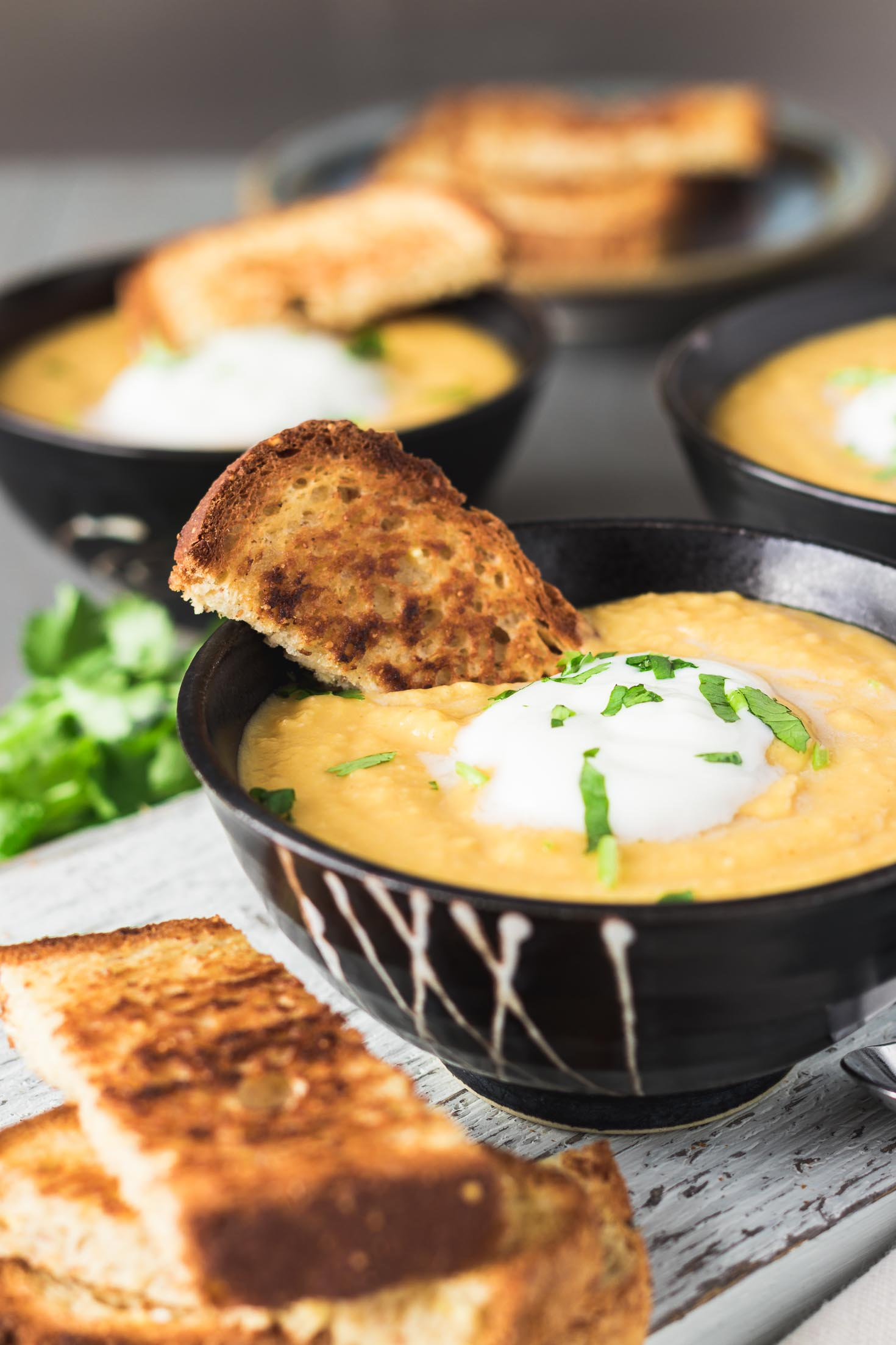 Navy Bean Garam Masala Carrot Soup-sideview-soup in one bowl with toasted bread and garnished with yogurt and fresh cilantro leaves