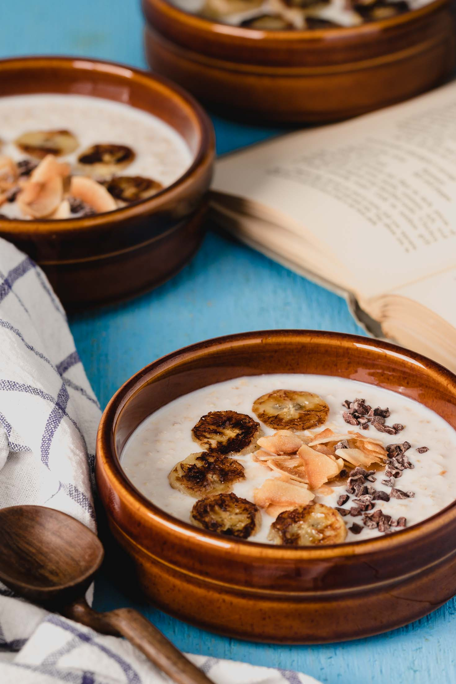 Caramelized Banana Overnight Oats-front view-in three bowls with a wooden spoon