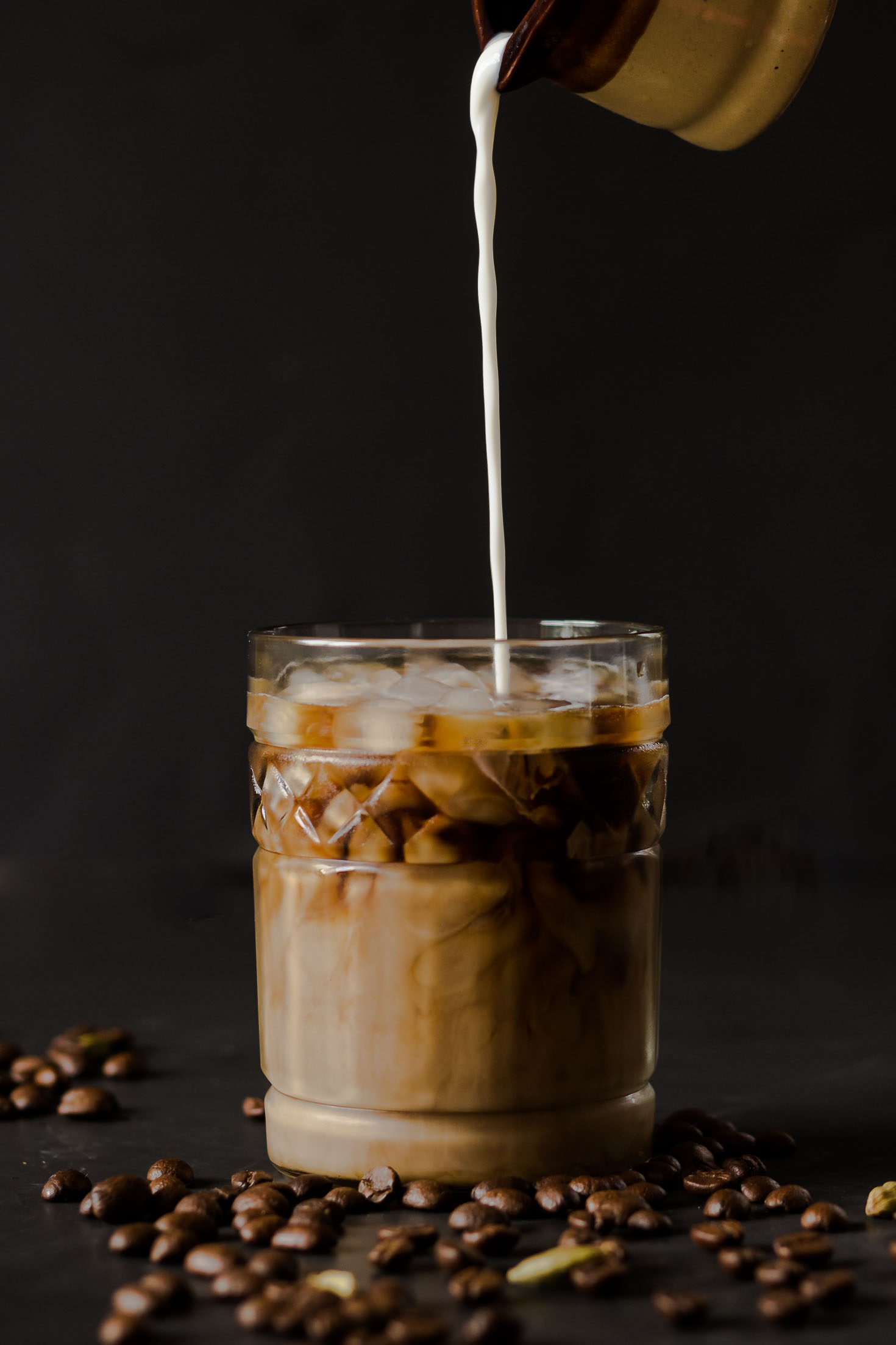 Cardamom Cold-Brewed Coffee-Front view-creamer is pouring into a glass of iced coffee with coffee beans and cardamom pods as foreground.