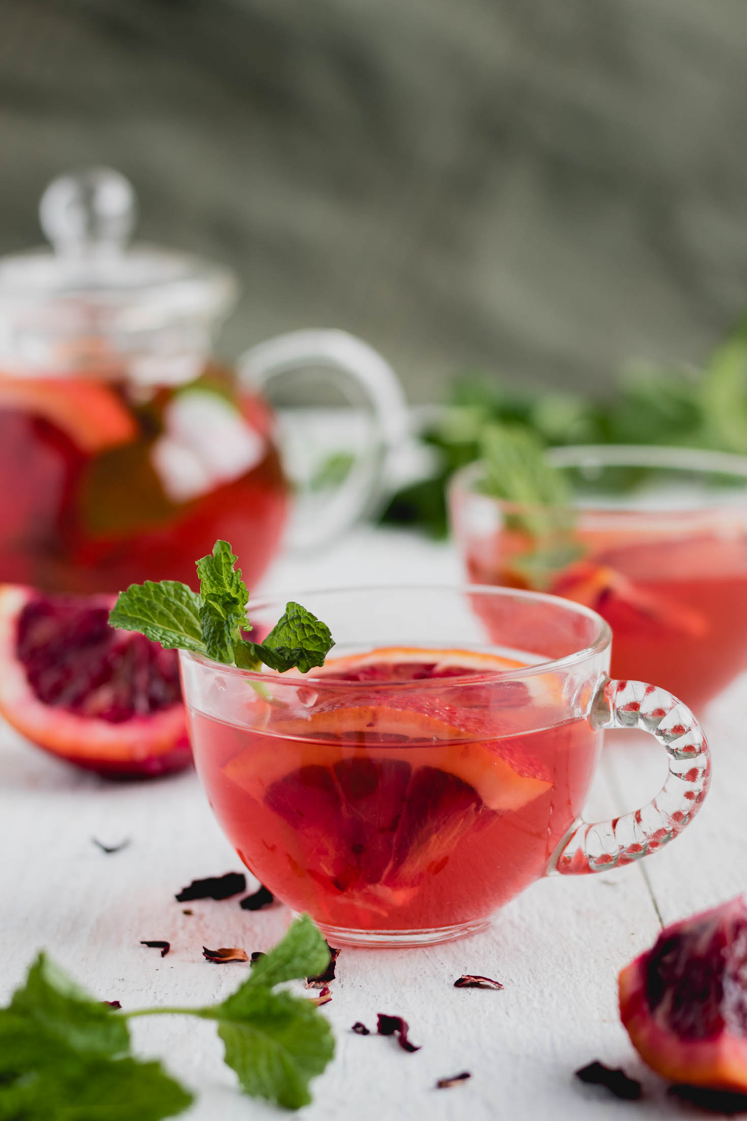 Hibiscus Orange Mint Water Kefir-front view-a small glass garnished with blood orange and fresh mint sprig