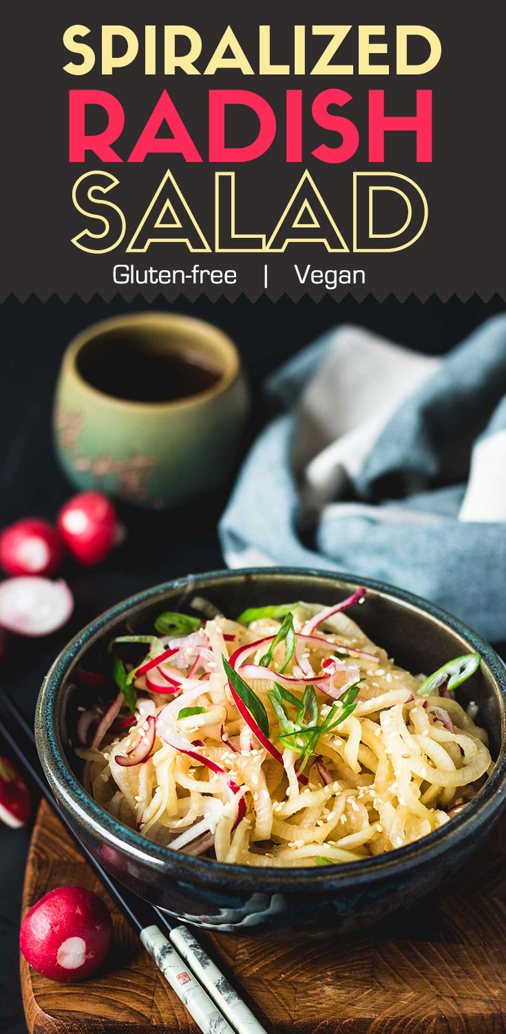 Spiralized Radish Salad-in a dark green bowl-garnished with chopped green onion and white sesame seeds