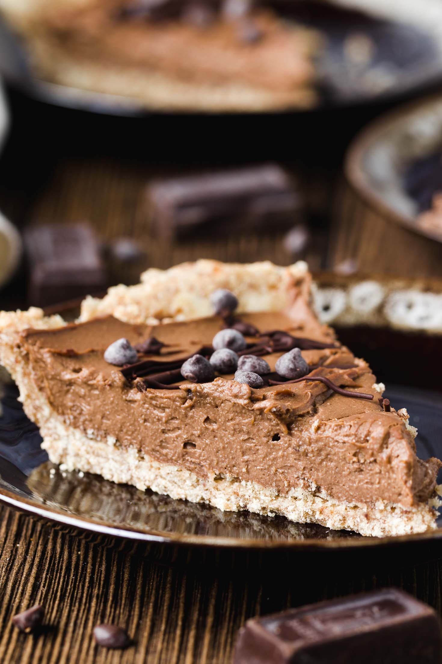 Vegan Cashew Butter Silky Chocolate Pie-a piece of pie in a brown plate, garnished with melted chocolate and chocolate chips