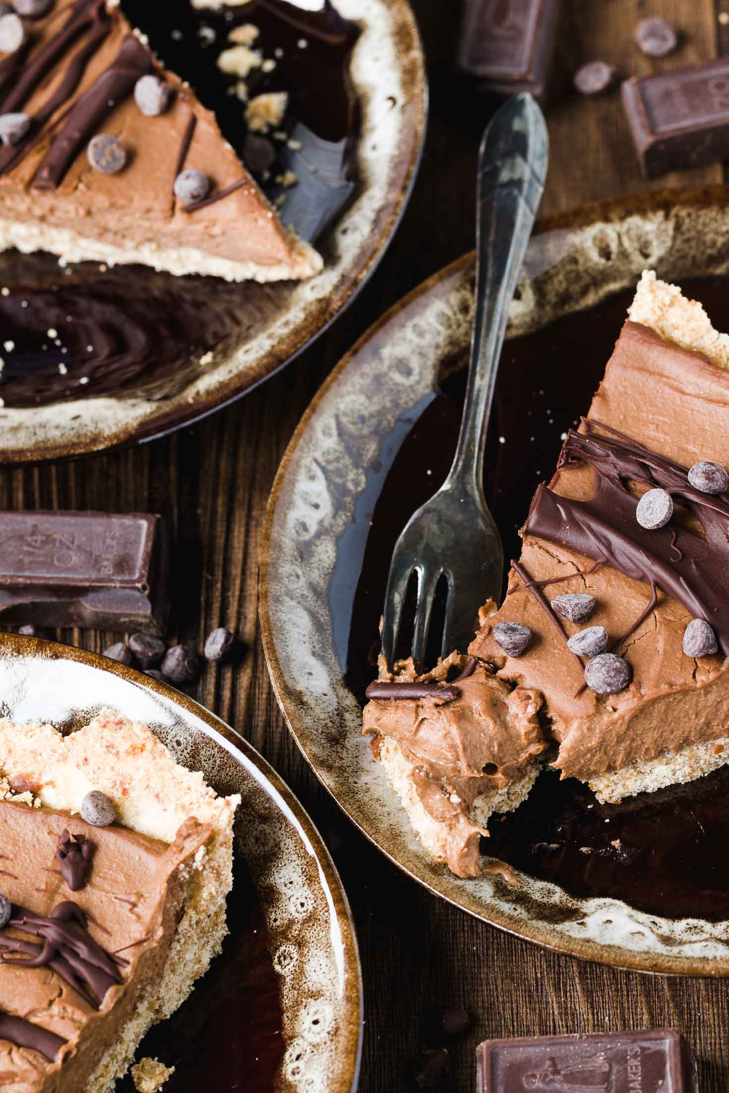 Vegan Cashew Butter Silky Chocolate Pie-top view-three pieces of pie in three brown plate, garnished with melted chocolate and mini chocolate chips