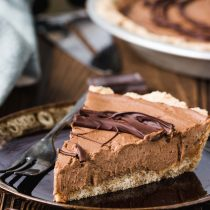 Vegan Cashew Butter Silky Chocolate Pie-top view-one piece of pie in a brown plate, garnished with melted chocolate