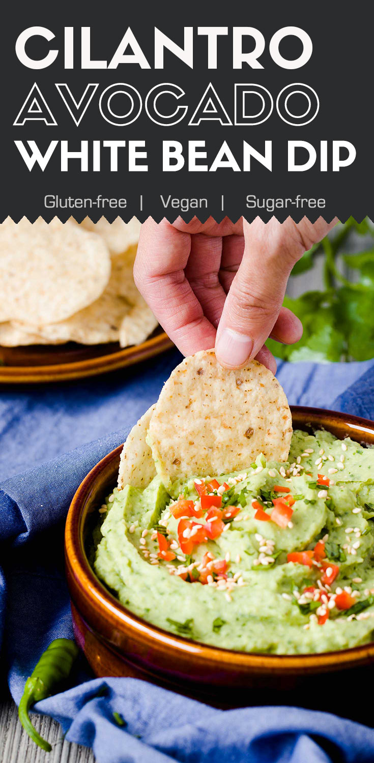 Cilantro Avocado White Bean Dip-top/side view-in a brown serving bowl with corn chips dipping into the dip-graphic