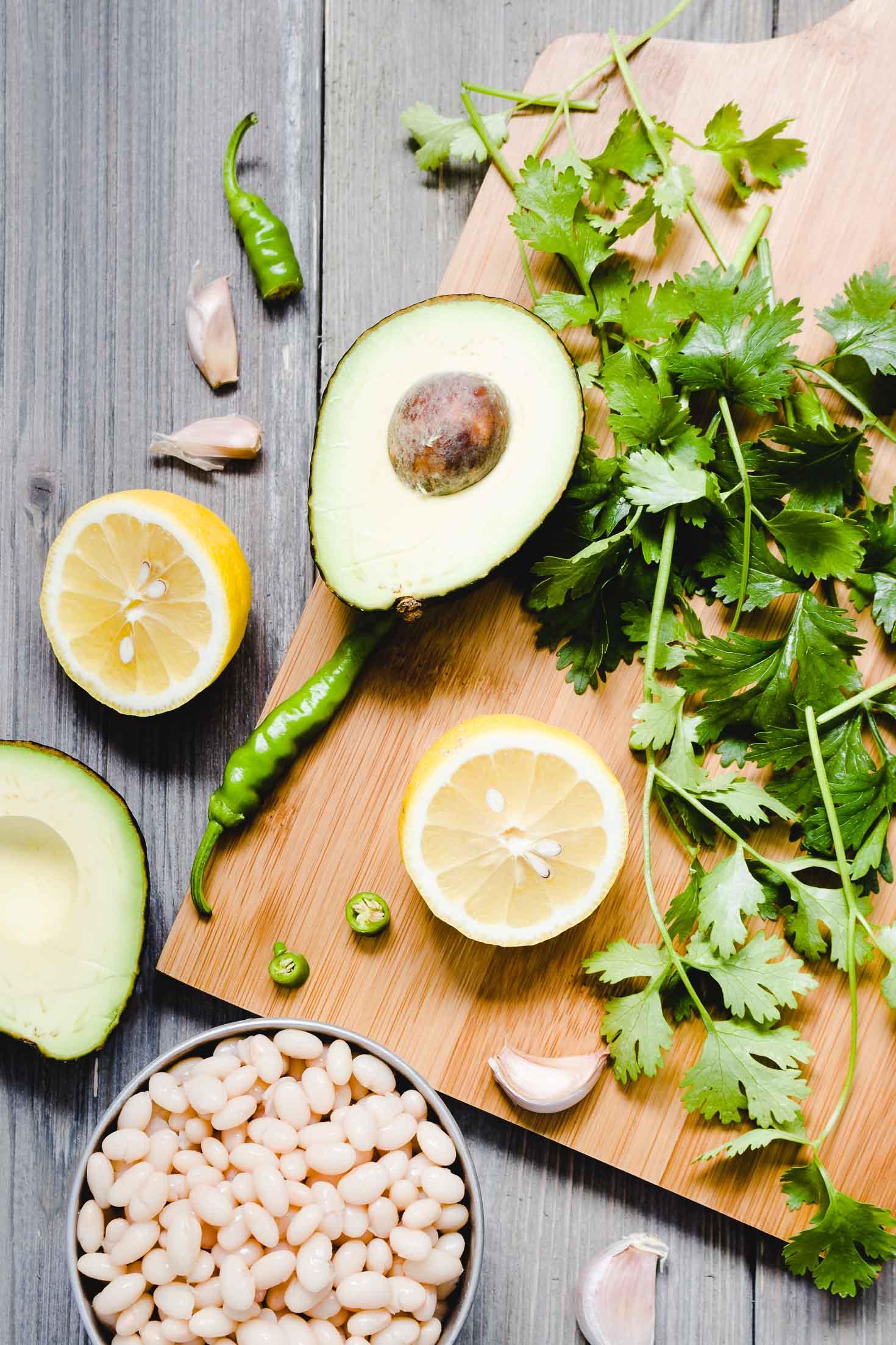 Cilantro Avocado White Bean Dip-top view-ingredients-cooked navy beans, garlic, green chili, cilantro, lemon, avocado