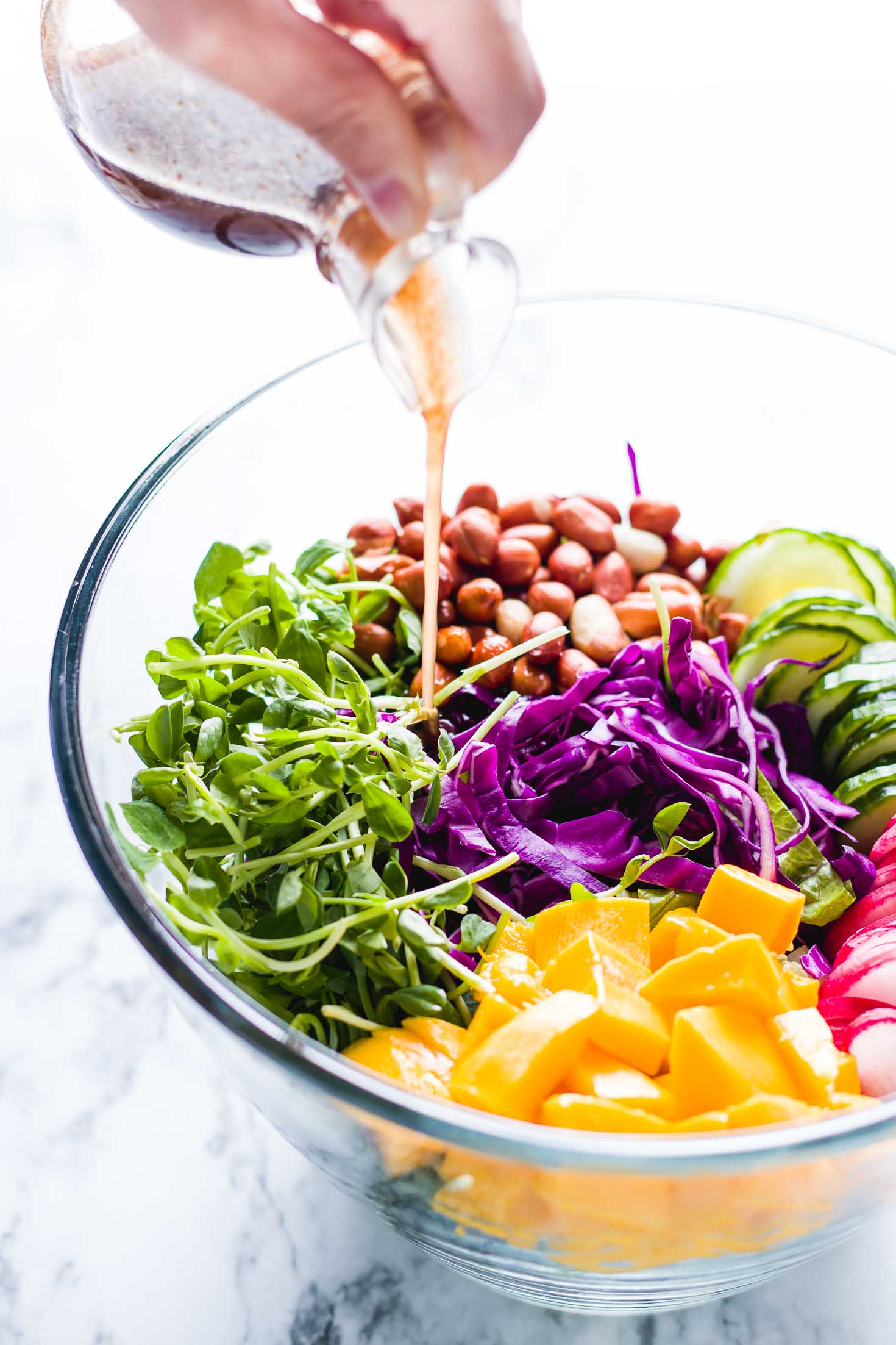 Pea Shoots Mango Rainbow Salad-all ingredients in a glass bowl before mixing them together. Salad is served with balsamic vinaigrette.