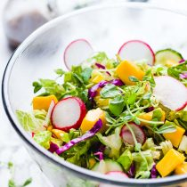 Pea Shoots Mango Rainbow Salad-in a glass serving bowl.
