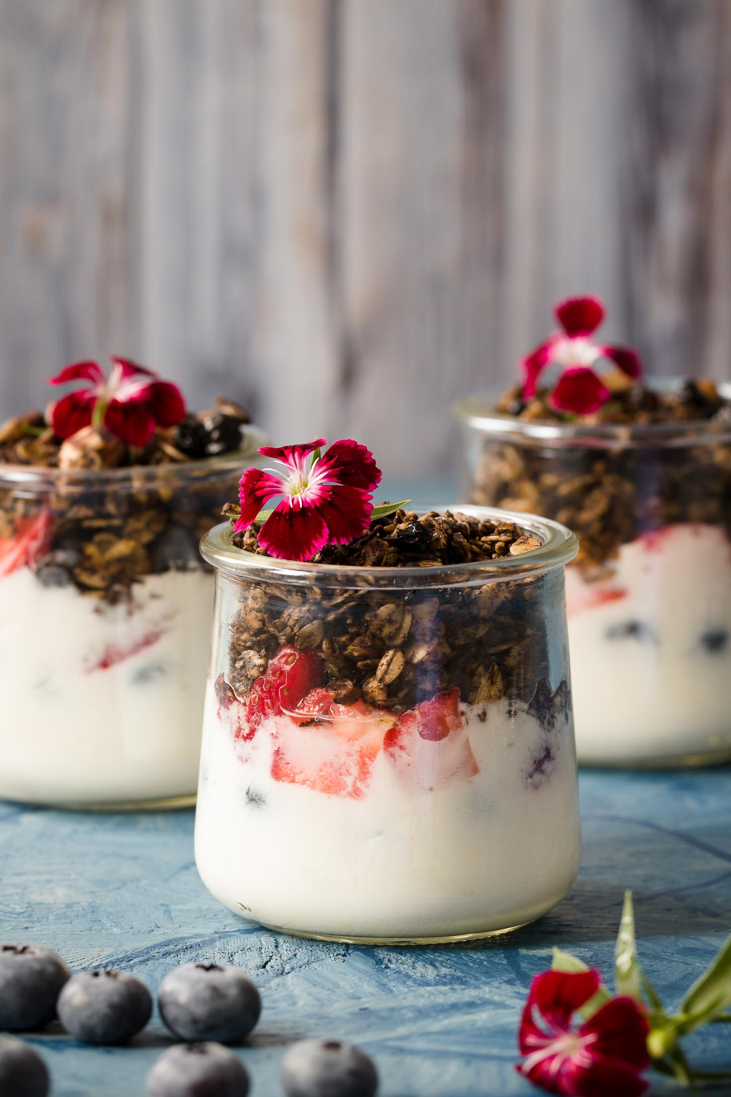 Pistachio Chocolate Granola-front view-three jars of parfait granola-yogurt blueberries and granola garnished with red dianthus flower