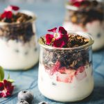 Pistachio Chocolate Granola-small square image-three jars of parfait granola-yogurt blueberries and granola garnished with red dianthus flower